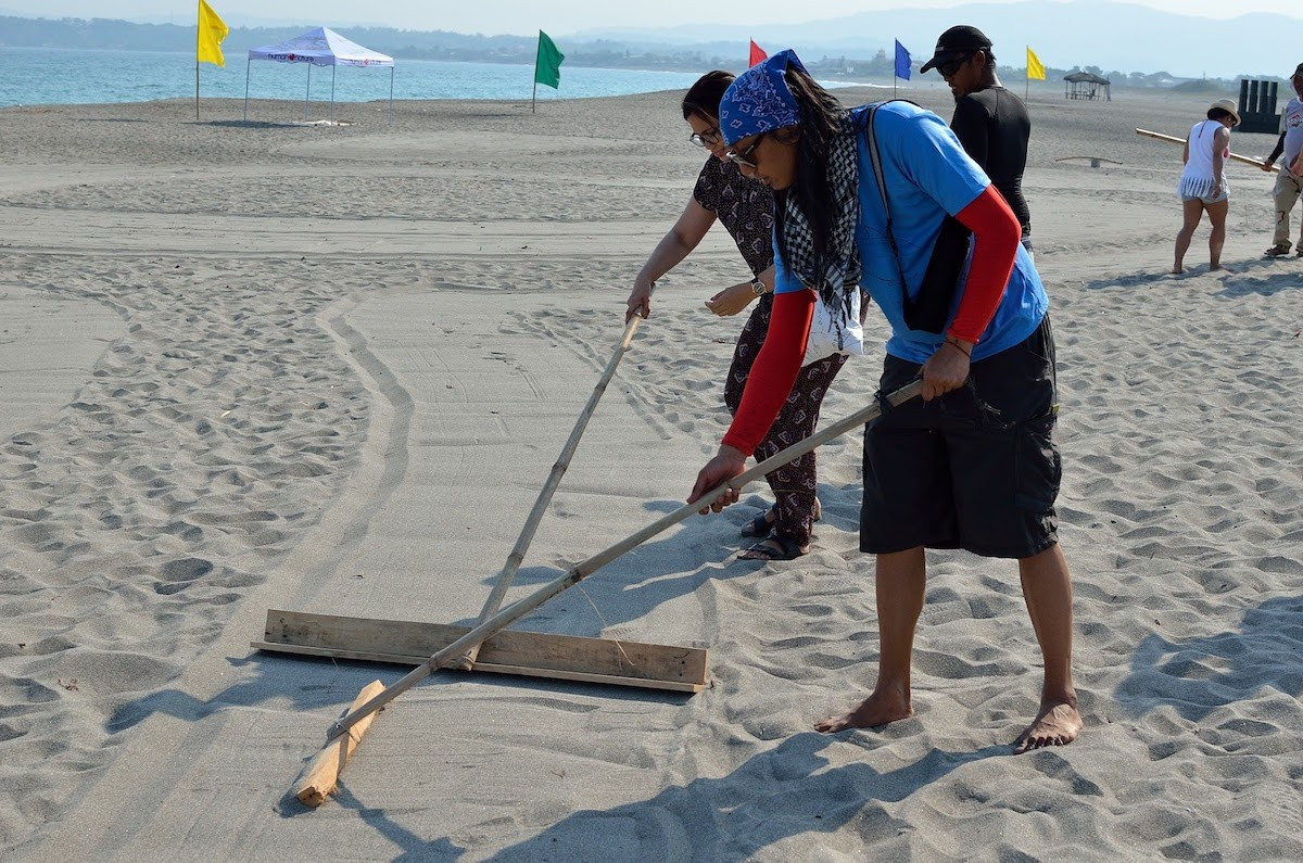 Artist AG Sano leading the creation of sand art.